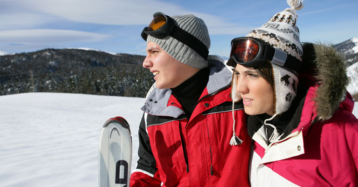 a young couple in ski gear on a mountain