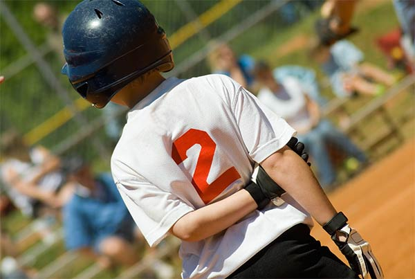 back of young baseball player wearing helmet