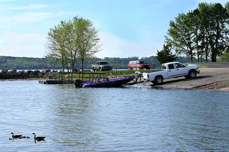Purple boat being launched into water by a white pickup truck