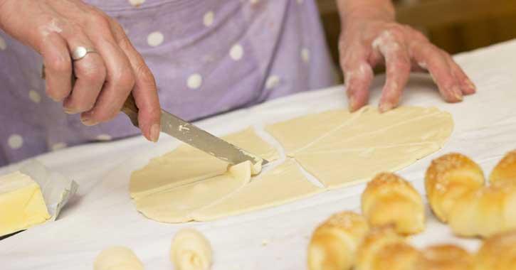 Woman cutting dough for rolls