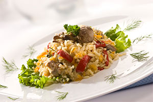 rice with peppers and mushrooms garnished with dill on a white plate