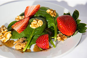 spinach, strawberries, walnuts, and dressing on a white plate